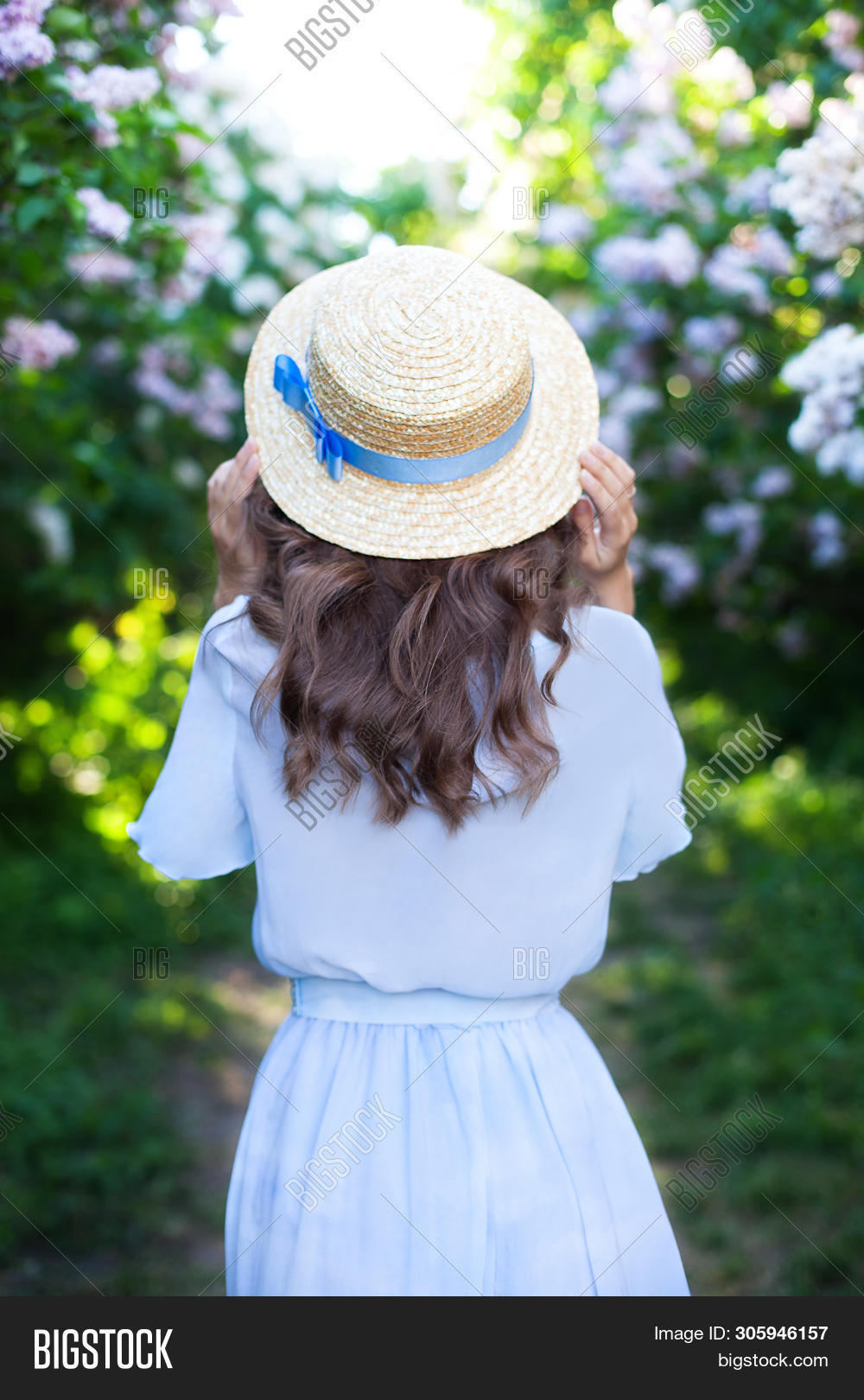 Girl In A Straw Hat With A Blue Ribbon On A Spring Afternoon. Back View. Trendy Casual Summer Or Spr
