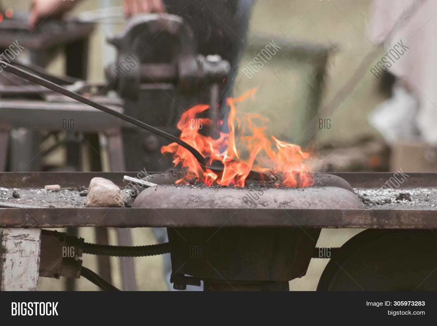 Blacksmith Handles Pig Iron In A Blacksmith`s Forge.close Up Of Hands Of Blacksmith Working With Iro