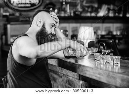 Alcohol addicted concept. Hipster brutal man drinking alcohol ordering more drinks at bar counter. Guy spend leisure in bar with alcohol. Man drunk sit alone in pub. Alcoholism and depression stock photo