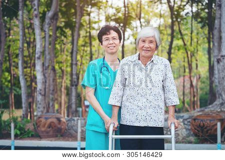 Smiling caregiver Senior nurse take care a Senior patient in walker for relaxing and looking around park stock photo