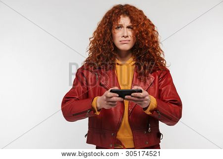 Portrait of displeased redhead woman 20s wearing leather jacket frowning and holding mobile phone isolated over white background stock photo