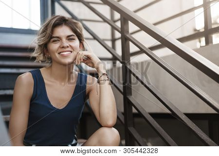 Sassy good-looking european blond young girl enjoy summer sunny day sit stairs relaxed casually smiling talking have fun, discuss recent journey abroad, have pleasant conversation look camera stock photo