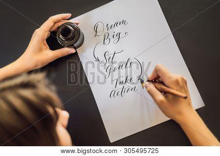 Dream Big Set Goals Take Action. Calligrapher Young Woman Writes Phrase On White Paper. Inscribing O