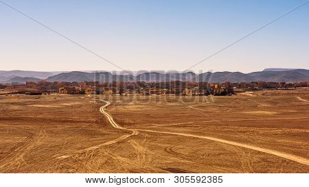 Dirt road going to the city of Ouarzazate in Morocco. Ouarzazate with typical moroccan architecture is nicknamed The door of the desert due to its location between Atlas Mountains and Sahara desert. stock photo