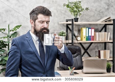 Drinking coffee relaxing break. Boss enjoying energy drink. Start day with coffee. Successful people drink coffee. Caffeine addicted. Man bearded businessman hold coffee cup stand office background. stock photo