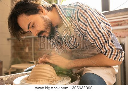 Young creative artisan bending over rotating clay item on wheel while using one of handtools for cutting and ornamenting stock photo