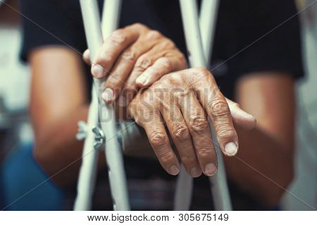 Hands of old man on crutches. Close-up a elderly man with crutches. stock photo