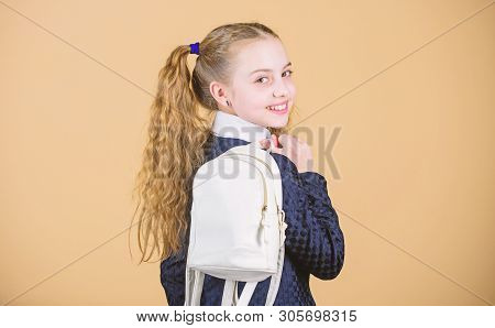 Carrying things in backpack. Schoolgirl ponytails hairstyle with small backpack. Learn how fit backpack correctly. Girl little fashionable cutie carry backpack. Popular useful fashion accessory stock photo