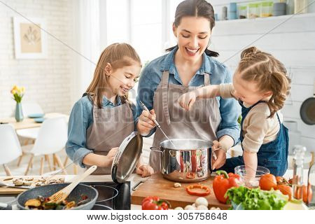 Healthy food at home. Happy family in the kitchen. Mother and children daughters are preparing vegetables. stock photo