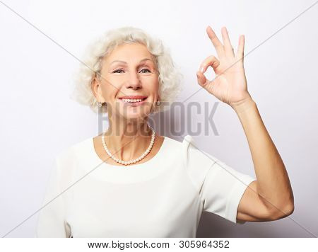 happy charming cheerful excited with beaming toothy smile mature lady grandmother granny grandma, she is showing okay sign stock photo