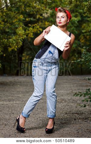 Beautiful pin-up girl in denim overalls and a red bandana holding copyspace stock photo