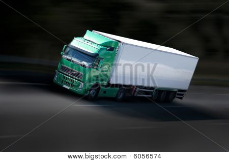 A green and black semi-truck on the highway stock photo