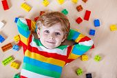 Little Blond Child Playing With Lots Of Colorful Plastic Blocks Indoor