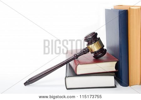 Law concept - Law book with a wooden judges gavel on table in a courtroom or law enforcement office isolated on white background. Copy space for text. stock photo