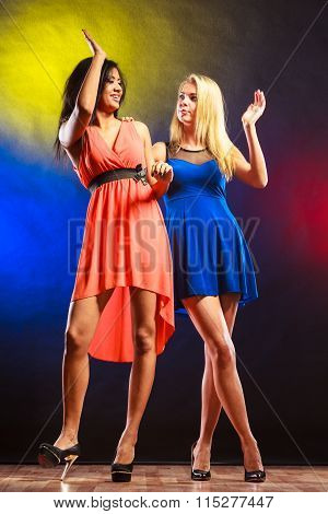 Party celabration carnival. Two attractive funny dancing women in dresses on colorful background in studio. stock photo