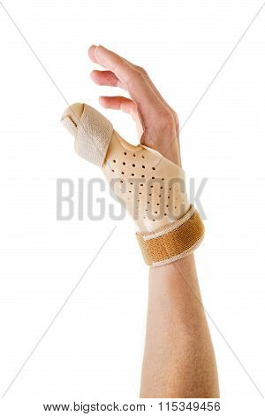 Close Up of Human Hand Wearing Brace Over Thumb in Studio with White Background stock photo