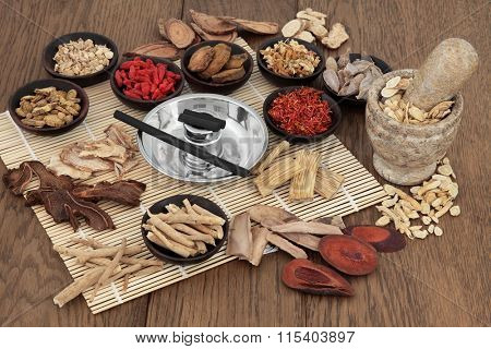 Moxa sticks and chinese herbs used in traditional herbal medicine with mortar and pestle over bamboo and oak background. stock photo