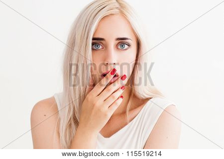 Surprised girl covers her mouth and her eyes wide open. A conceptual photo on a white background stock photo