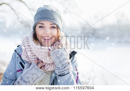 Beautiful  happy laughing young woman wearing winter hat gloves and scarf covered with snow flakes.
