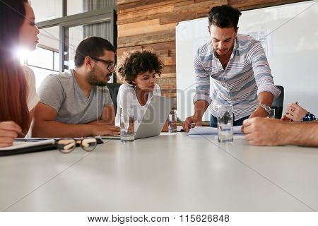 Leader Showing Business Plan To Colleagues During A Meeting