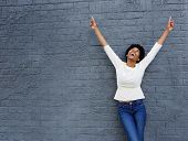 Cheerful African Woman With Hands Raised Pointing Up