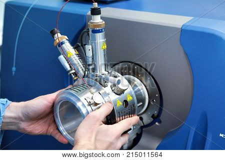 Adjust the mass spectrometer. The man analyzes the device for determining the masses of atoms. Device for the pharmaceutical industry. Ionic source of mass spectrometer. stock photo
