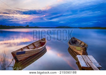Travel Destinations Concepts. Tranquil and Peaceful Picturesque Landscape of The Strusto Lake with Wooden Boats at Foreground. Lake is a Part of National Braslav Lakes Reserve. Horizontal Image