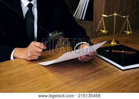 Male lawyer reading legal contract agreement and examining documents with magnifying glass in courtroom. stock photo