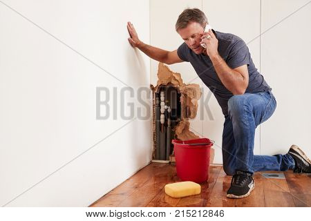 Middle aged man with a burst water pipe phoning for help stock photo