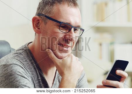 Hearing impaired man with hearing aid using smart phone at home or at office stock photo