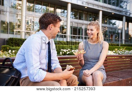 Businessman And Businesswoman Eating Lunch Outside Office stock photo