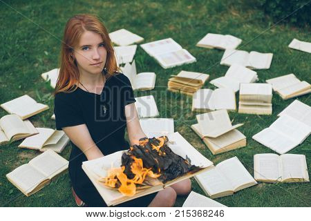 A Girl Holding A Book Burning In Nature In Summer Garden