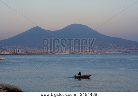 Mt.Vesuvius view from Naples at dusk. A boat chugs along the Bay of Naples. Mt.Vesuvius an active volcano near the city of Naples Italy. The volcano is a realistic threat for about 3 million people living in Naples and surrounding towns. stock photo