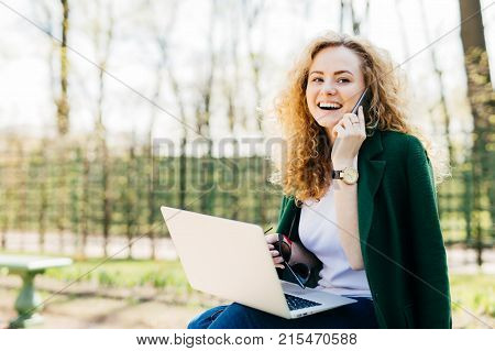 Attractive woman with trendy hairdo sitting in park communicating over her cell phone using modern laptop computer having broad smile while looking aside. People technology communication concept stock photo