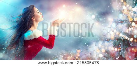 Christmas Winter Fashion Girl blowing  Magic snow in Her Hand. Fairy. Beautiful New Year and Xmas Tr