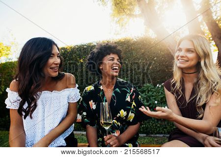Happy young female friends hanging out and talking at outdoors party. Group of young women sitting outdoors with drinks and talking.
