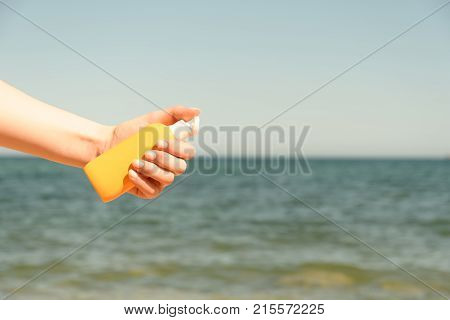 Female hand holds the bottle against a sandy beach and sea in bright Sunny day from left side of frame more yellow stock photo