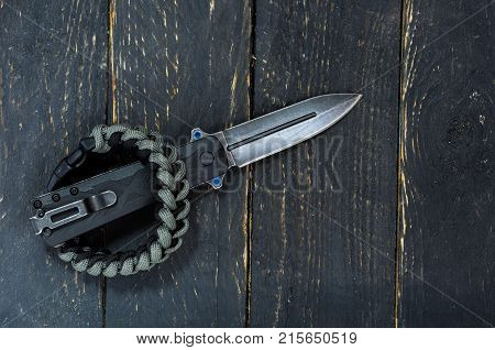 Army knife with a clip and bracelet for survival. Low key. stock photo