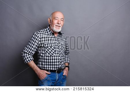 Serious senior man posing with hands on hips, gray studio background, copy space stock photo