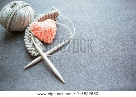 Set for knitting: knitting needles corded cotton yarn started knitting and pink heart of thread on dark felt background. Grey Yarn ball and heart shape Yarn with knitting needles. Knitting as a kind of cozy needlework. stock photo