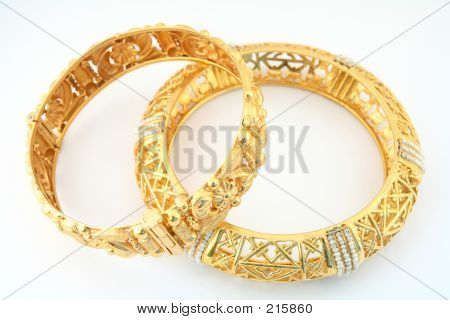a pair of 22k gold bracelets in the arab or indian fashion, one of them inset with small gulf pearls. stock photo