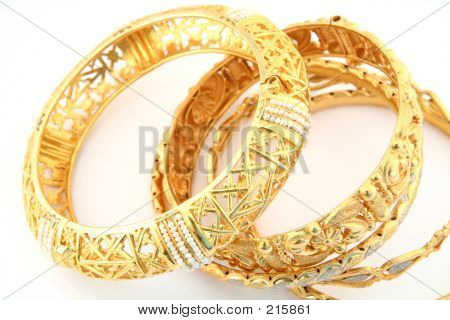 a collection of traditional arabian or indian-style 22k gold bracelets, one of them inlaid with natural gulf pearls stock photo