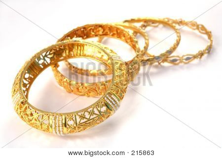a group of 22k gold bracelets, showing details of the workmanship. the one at the front is inlaid with small gulf pearls. the style is arabian or indian/eastern. stock photo