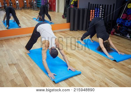 Man and woman doing yoga exercises on mats at gym hall. stock photo