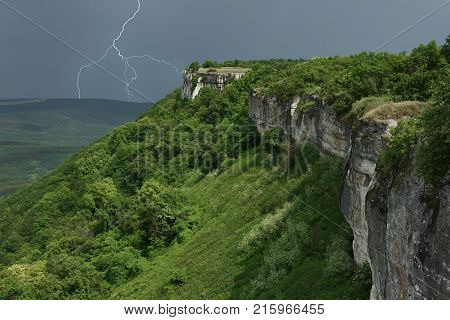 Landscape with thunderstorm in mountains. The approaching storm front over mountains. The dividing line of solar weather and stormy weather in Crimea.