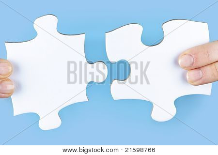 Fingers joining large white blank jigsaw puzzle pieces stock photo