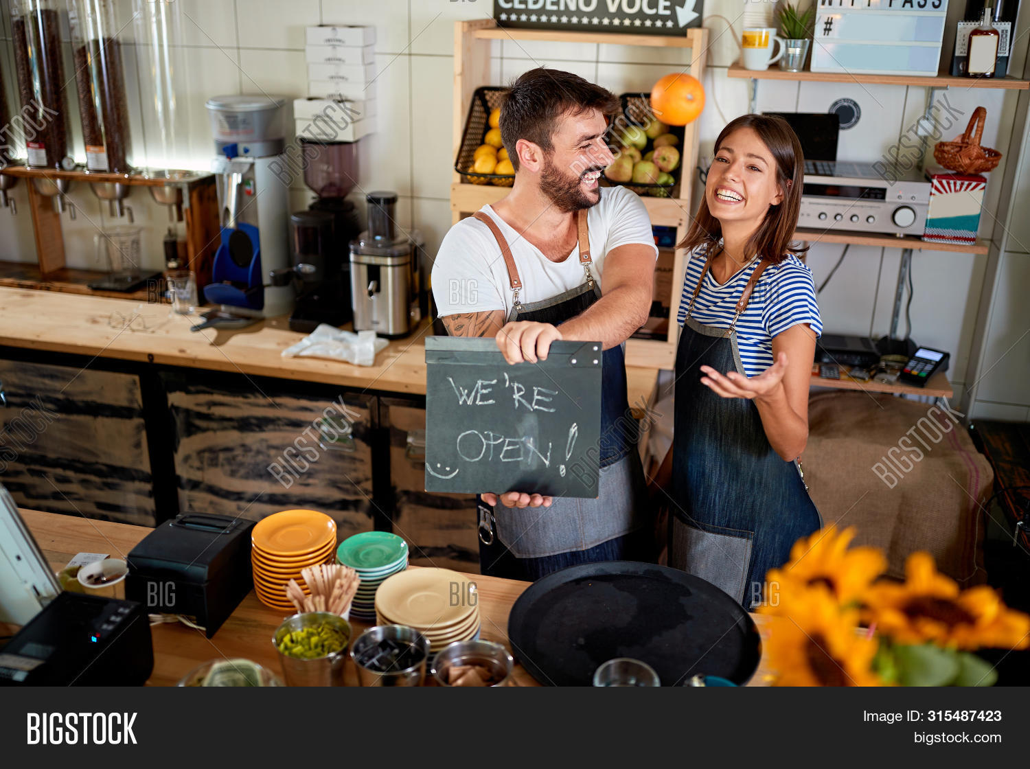 apron,bar,barista,business,businessman,businesswoman,cafe,cafeteria,caucasian,cheerful,coffee,company,concept,couple,employee,equipment,female,happy,internet,job,laptop,leader,lifestyle,male,man,manager,men,modern,open,owner,partner,people,professional,proud,shop,sign,small,smiling,store,success,technology,two,wireless,woman,work,working,workplace,young