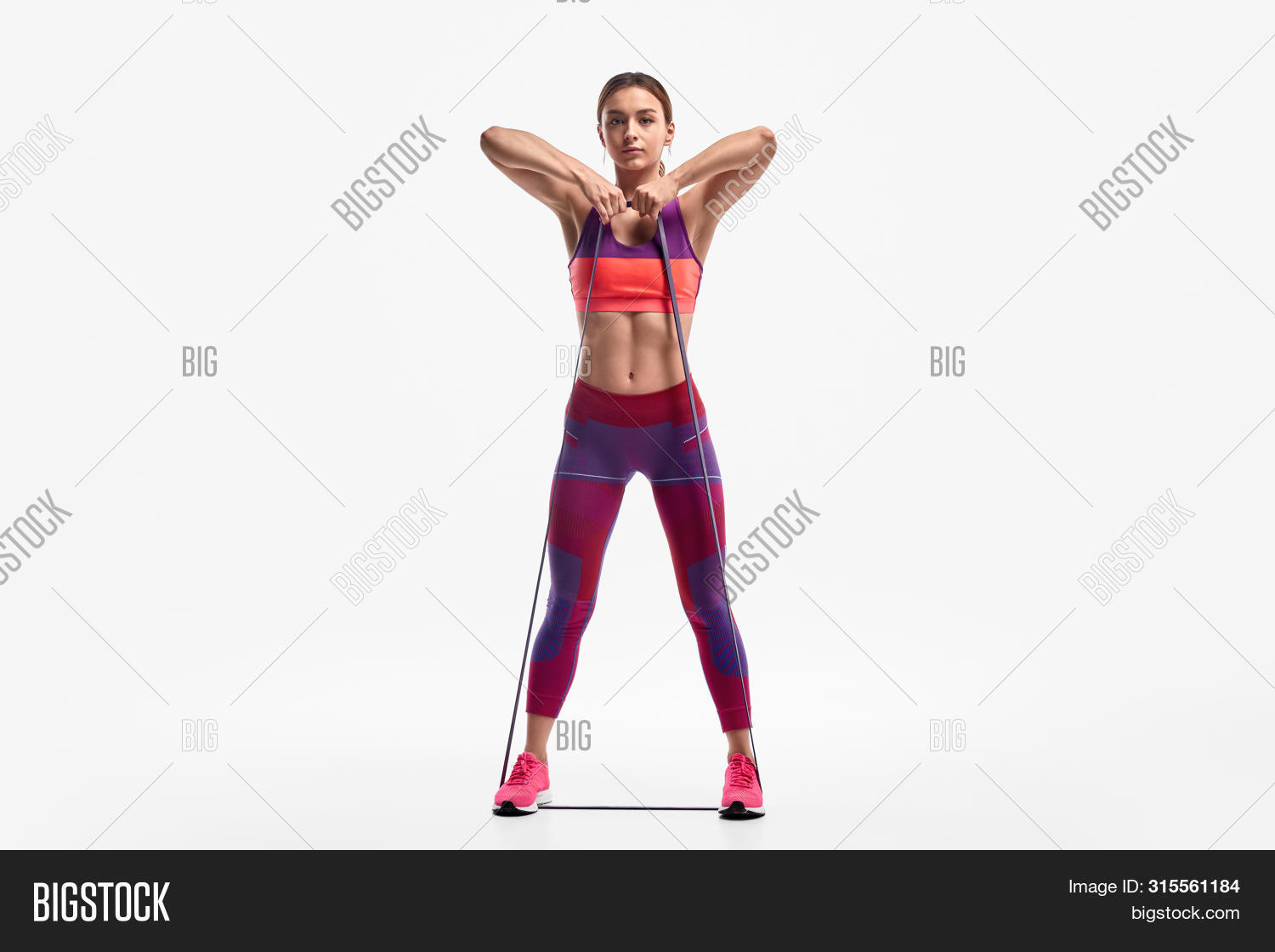 Full length determined young woman in sportswear looking at camera and pulling resistance band to chest while standing against white background