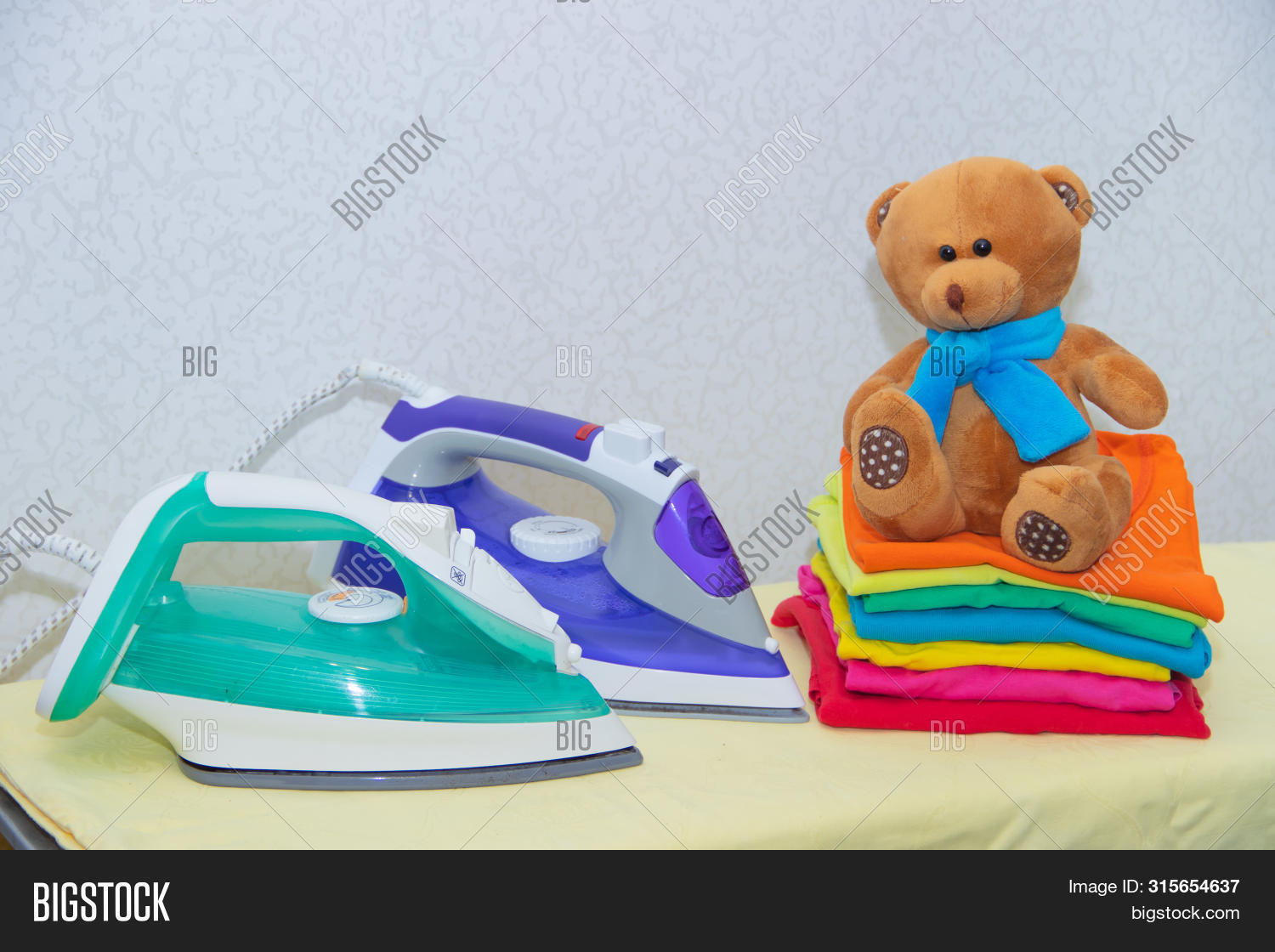 Iron And Baby Clothes. Colored Clothes On An Ironing Board. Bright T-shirts. Ironed Colored Baby Und