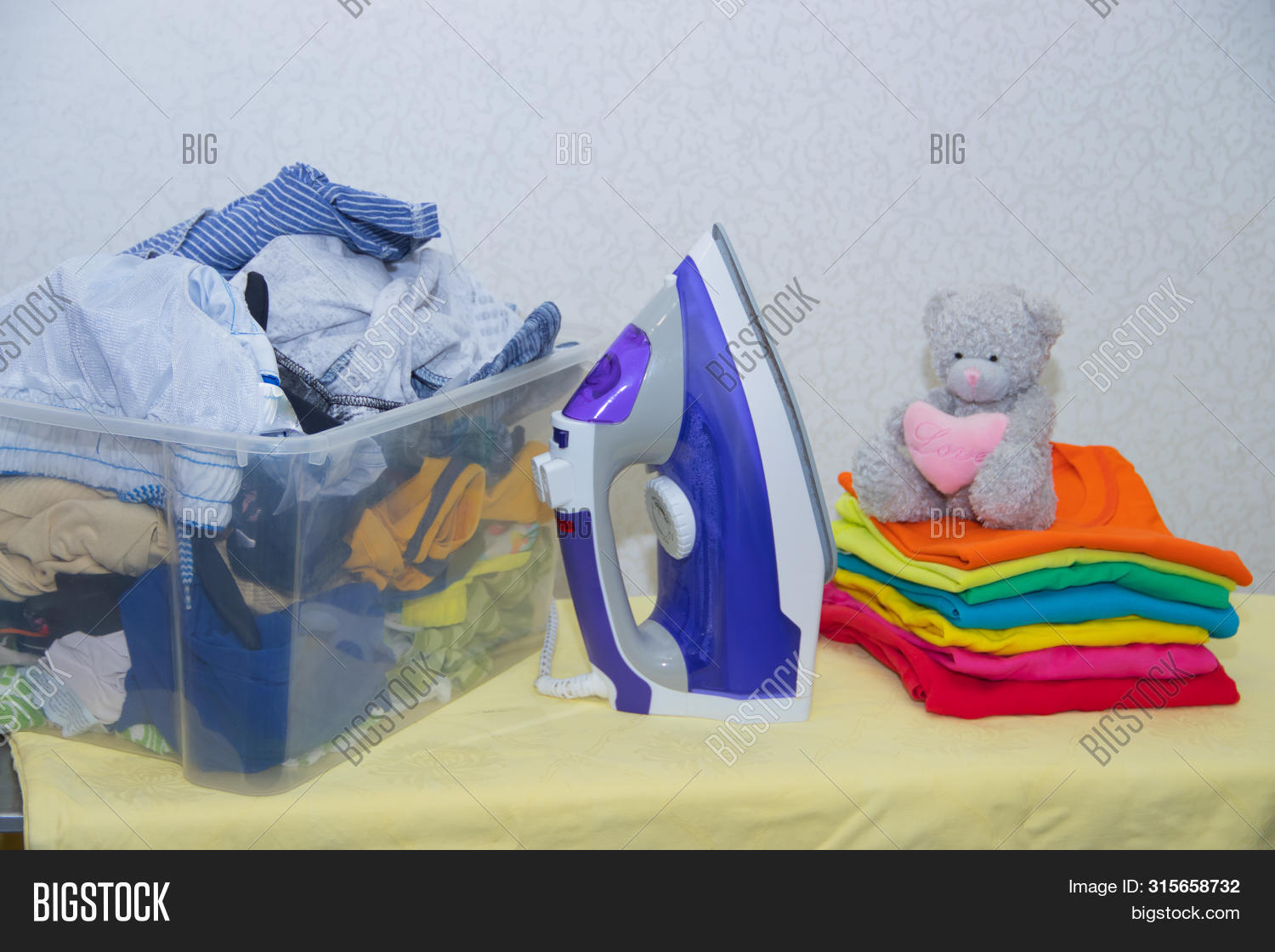 Iron And Baby Clothes. Colored Clothes On An Ironing Board. Bright T-shirts. Ironed And Non-ironed C